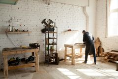 Joiner working at workbench in small carpentry. Image of woodworking workshop with electric instruments on shelves, joiner working at workbench, dried wooden stock photo