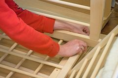 Joiner zbiera nowego dziecka łóżko polowe z handtool Mężczyzna podnosi up dziecka ` s drewniany ściąga czekaj dziecka fotografia royalty free