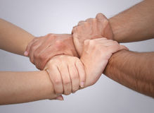 Joining Hands. Male and female hands in a square shape. Grey colored background Stock Photo