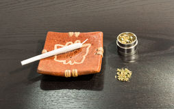 Joint in the ashtray and metal grinder with marijuana.  stock photography