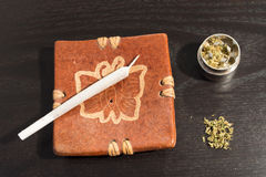 Joint in the ashtray and metal grinder with marijuana.  royalty free stock image