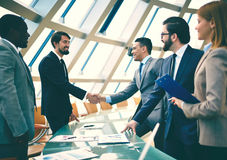 Joint business. Group of business people looking at their colleagues handshaking after striking grand deal royalty free stock images