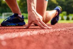 Joint care for runners. Hand of sportsman on running track low start position. Runner ready to go close up. Ultimate. Remedies. Flexibility is ability to Stock Photography
