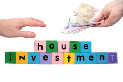 Joint house investment in toy block letters. Toy letters that spell house investment with cash in hands against a white background with clipping path Royalty Free Stock Photography