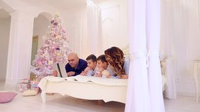 Joint leisure of large and friendly family with gadget on bed in bright bedroom with Christmas tree and decorations. stock video