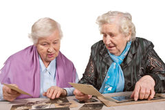 Joint memories. Two old women together looking at vintage photographs Stock Photography