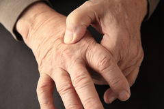 Joint pain on hand of older man. Senior man indicates where he feels pain on the back of his hand royalty free stock images
