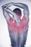 Joint pain. Rear view of young muscular African man touching his neck and elbow while standing against grey background Royalty Free Stock Photos