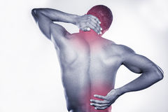 Joint pain. Rear view of young muscular African man touching his neck and hip while standing against grey background Stock Photo