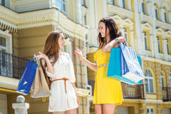 Joint purchases Two girlfriends hold shopping bags and walk arou Royalty Free Stock Images
