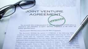 Joint venture agreement approved, seal stamped on official document, business. Stock photo royalty free stock images