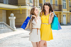 Joint walk. Two girlfriends holding shopping bags and walk aroun Stock Images