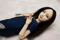 Jointed doll in a blue dress with a brooch royalty free stock image