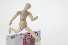 Jointed doll jumping over a 500-Euro-Banknote Stock Images