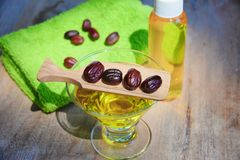 Jojoba oil and seeds on a wood surface. Jojoba oil in a glass bottle and jojoba seeds near on a wood background, green towel, close up stock photography