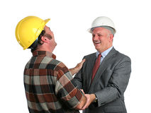 Joke On the Job. An engineer and a construction foreman sharing a joke together at work - isolated Royalty Free Stock Images