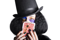 Joker with burnt playing card. Woman with black top hat and long hair holding burnt playing card, white background Stock Photo