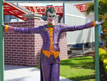 Sculpture of The Joker. The sculpture of The Joker - Batmans adversary - in a Theme Park setting. Roller coaster tracks in the background Royalty Free Stock Photography