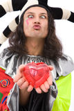 Joker in love. Love concept with joker holding a heart shape and sending a kiss Royalty Free Stock Photo