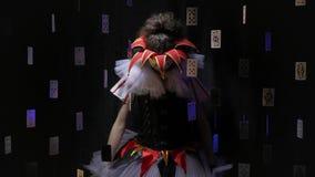 Jokerkvinnan med makeup och en färgrik klänning står i mörkret som en docka tappar därefter hennes huvud och armar som är långsam arkivfilmer