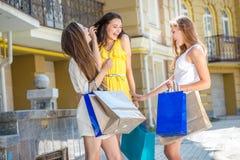 Jokes girlfriends. Girls holding shopping bags and walk around t Stock Image