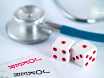 Joking around with your health. Two Joker Cards and a Stethoscope and two dice - gambling with your health Royalty Free Stock Images