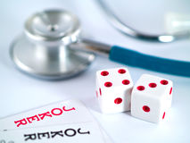 Joking around with your health. Two Joker Cards and a Stethoscope and two dice - gambling with your health Stock Images