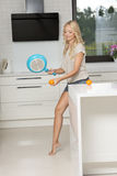Joking house wife playing tennis. Very pretty young blond girl in shorts playing tennis in funnny way , with a pan and an orange fruit in a modern kitchen Royalty Free Stock Photos