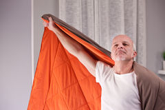 Joking man uses quilt as a cloak Royalty Free Stock Photography