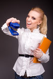 Jokingly Agressive Young Girl With Stapler On Dark Royalty Free Stock Photos