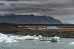 JOKULSARLON,冰岛- 2014年10月17日:Jokulsarlon有旅游汽车的冰川盐水湖 山和多云天空在背景中 库存照片