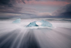 Jokulsarlon. Blue ice piece on the beach with a hole in Royalty Free Stock Photo