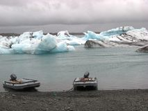 Jokulsarlon Boats. Rubber boats at the shore of Jokulsarlon glacier lake with icebergs under the threatening grey skies of Iceland Royalty Free Stock Photos