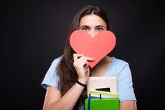 Joli étudiant avec la carte de coeur dans sa main Images libres de droits
