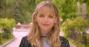 Joli étudiant blond caucasien observant dans la caméra étant calme et fixe en parc vert de ville banque de vidéos