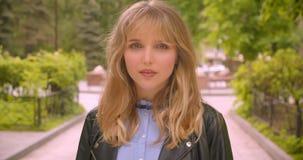 Joli étudiant blond caucasien posant dans la caméra souriant séduisant et joyeux en parc vert de ville banque de vidéos