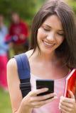 Joli étudiant envoyant un texte dehors sur le campus Photos stock