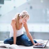 joli étudiant féminin avec l'ordinateur portatif et les livres photos stock