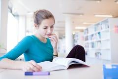 Joli étudiant universitaire féminin dans une bibliothèque Photo stock