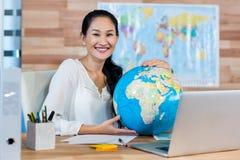 Joli agent de voyage tenant le globe et souriant à l'appareil-photo Image libre de droits