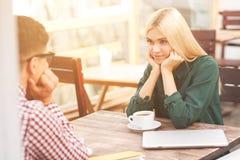 Joli ami et amie détendant dans le cafétéria Image libre de droits