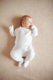 Joli bébé dans des pyjamas blancs se trouvant sur son stylo de dos et de participation dans la bouche Images stock