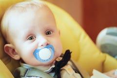 Joli bébé garçon s'asseyant dans Seat jaune avec Soother Photos stock