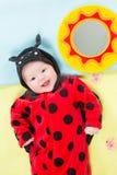 Joli bébé, rectifié dans le costume de coccinelle Photo stock
