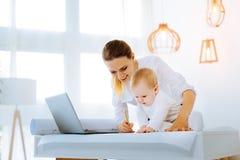 Joli bébé s'asseyant sur un dessin de sa mère Photo libre de droits