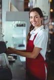 Joli barman regardant l'appareil-photo et à l'aide de la machine de café Images libres de droits