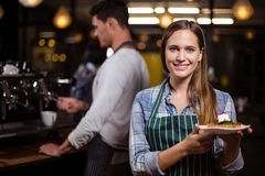 Joli barman tenant le dessert et souriant à l'appareil-photo Images libres de droits