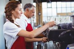 Joli barman utilisant la machine de café avec le collègue derrière Photos libres de droits