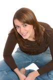 Joli brunette s'asseyant les jambes croisées photographie stock libre de droits