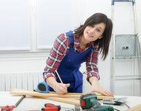 Joli constructeur de fille mesurant une planche de bois photographie stock libre de droits